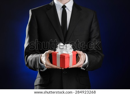 Theme holidays and gifts: a man in a black suit holds exclusive gift wrapped in red box with white ribbon and bow on a dark blue background in studio - stock photo