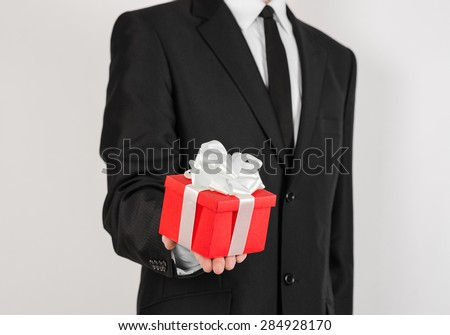 Theme holidays and gifts: a man in a black suit holds exclusive gift wrapped in red box with white ribbon and bow isolated on a white background in studio - stock photo