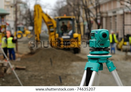 Theodolite, excavator and workers at road construction site - stock photo