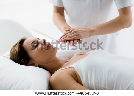 Theparist performing reiki treatment on young woman at spa