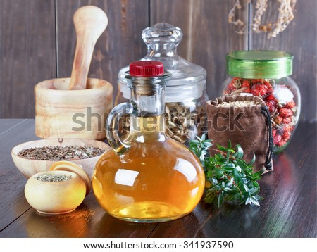 Therapeutic herbal tincture, alternative medicine, love potions, dried herbs on a wooden table. - stock photo