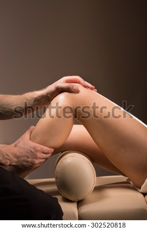Therapeutic massage performed to numb the knee pain - stock photo