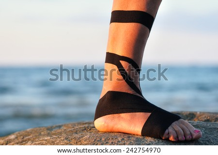 Therapeutic treatment of leg with black physio tape - stock photo