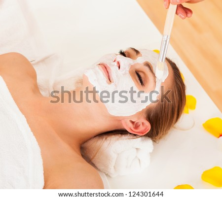 Therapist applying a face mask to the face of a beautiful young blonde woman using a cosmetic brush - stock photo