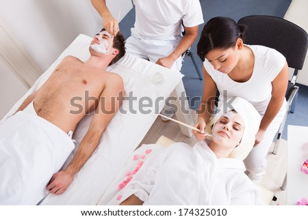 Therapist Applying Facial Mask To Young Couple At Beauty Salon - stock photo