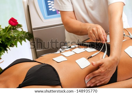 Therapist applying lipo massage on girls body in spa.  - stock photo