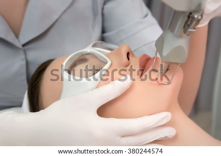 Therapist beautician makes a  laser rejuvenation for the model by  apparatus  in a beauty salon.  Close up, selective focus. - stock photo