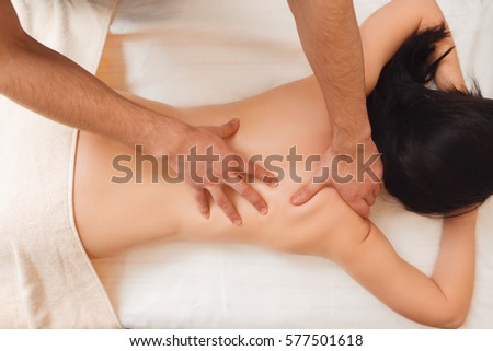 Therapist doing healing treatment on woman back. Chiropractic, osteopathy, dorsal manipulation. Alternative medicine, pain relief, resort concept