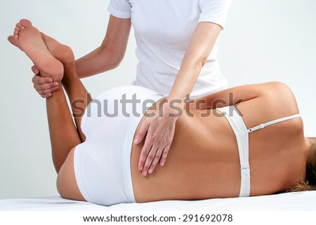 Therapist doing lower back massage on woman.Osteopath rotating woman legs. - stock photo