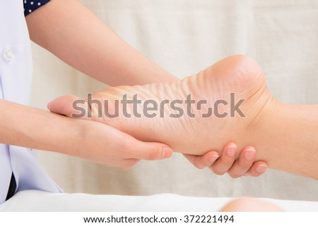 Therapist doing reflexology massage on woman foot in day spa - stock photo
