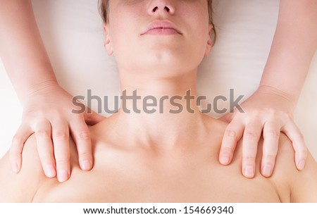 Therapist doing shoulders massage and pressing points to release tension in levator scapulae muscle