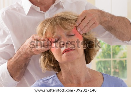 Therapist giving  temple massage  to middle aged woman