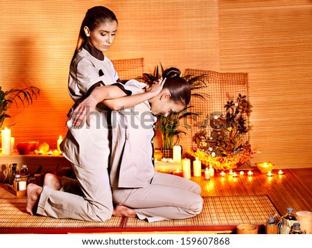 Therapist giving Thai stretching massage to woman. - stock photo
