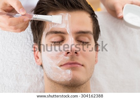 Therapist Hands With Brush Applying Face Mask To A Young Man In A Spa - stock photo