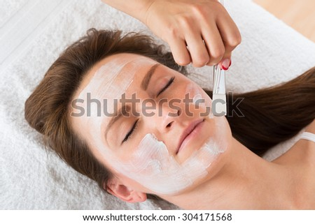 Therapist Hands With Brush Applying Face Mask To A Young Woman In A Spa - stock photo