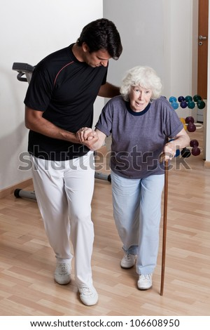 Therapist Helping Patient to walk with walking stick.