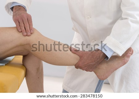therapist  knee examination for  woman patient in hospital - stock photo