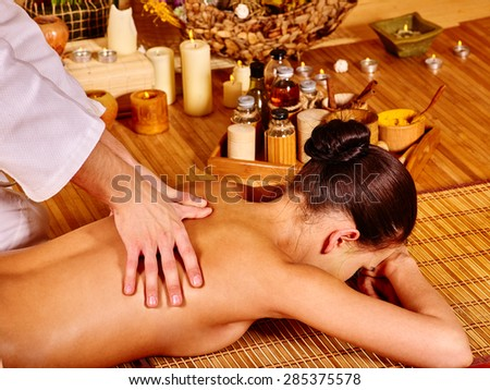 Therapist man giving oriental stretching massage to woman.