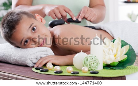 therapist massaging a young boy in the spa salon