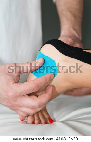 Therapist positioning kinesio taping on patient's foot