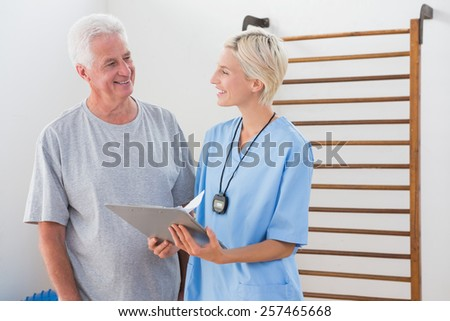 Therapist showing clipboard to senior man in fitness studio