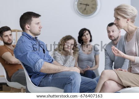 Therapist speaking to a man during group counseling session