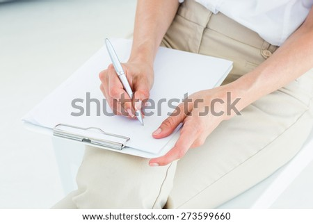 Therapist taking notes on white background - stock photo