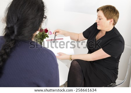 Therapist with customer at body shape clinic - stock photo
