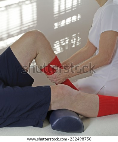 Therapist working on calf muscle   Female sports massage therapist working on male client's calf muscle while seated on couch with light coming through window blinds in background - stock photo