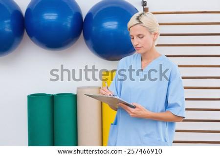 Therapist writing on clipboard fitness studio - stock photo