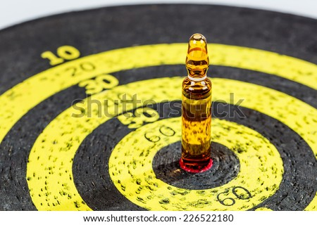 Therapy concept: drug ampule on old yellow target board. Shallow depth of field - stock photo