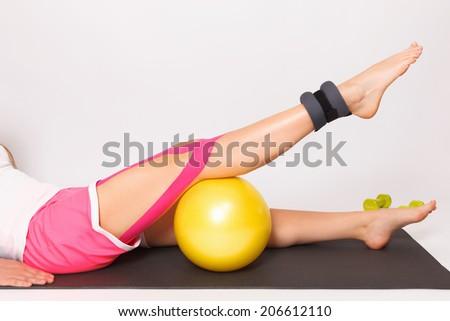 Therapy for leg injury with ball and kinesiology tape - stock photo