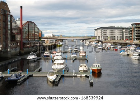 There are a lot of small pier with various boats, motorboats mooring in the river outlet. Trondheim is situated where the river Nidelva meets fjord with an excellent harbour. - stock photo