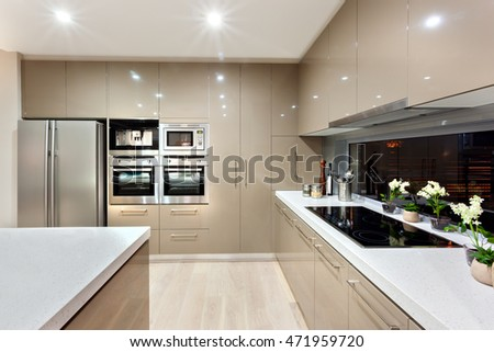 There are lots of wall cabinets and pantry cupboard fixed to the wall with A silver refrigerator and microwave oven. There are two ceramic counter top, both sides, one has black color modern stove