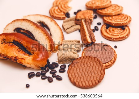 There are Pieces of  Roll with poppy seed,Cookies,Halavah,Chocolate Peas,Tasty Sweet Food on the White Background.Toned pink