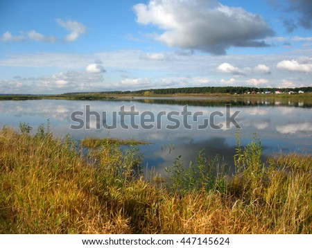 There are  river, sky and fall grass on bank - stock photo