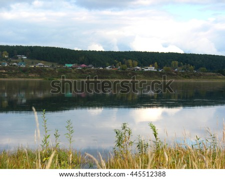 There are  river, sky and homes on bank - stock photo