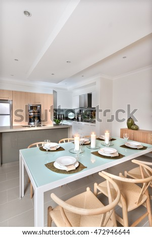 There are three white candles flashing top of the light blue and shiny dining table surrounded by white dishes and wine glasses. Wooden chairs around the small table in front of the kitchen counter