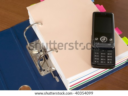 There is a block of documents and mobile phone