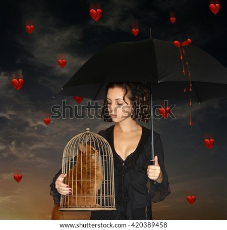 There is a girl with umbrella. She isl holding a cage with a cat.  Cracked hearts are falling from the sky instead of rain drops. - stock photo