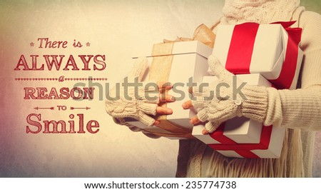 There is always a reason to smile holiday message with woman holding present boxes - stock photo