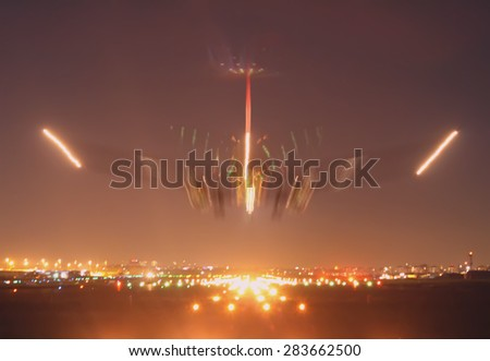 there is an aircraft just before the touch down with long exposure taking shows its landing movement - stock photo