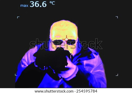 Thermal image of a man with the camera and temperature measurement - stock photo