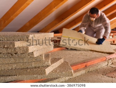 Thermal insulation of a building - mineral wool panels stack with man measuring in the background - stock photo
