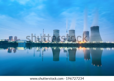thermal power plant in nightfall ,cooling towers and reflection in the river  - stock photo