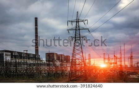 thermal power plant with tubes and high-voltage power lines at sunset
