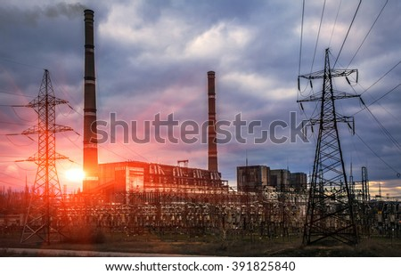 Thermal power plants with huge pipes and power lines at beautiful sunset