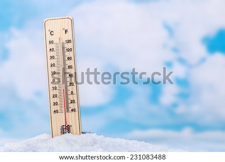Thermometer in snow against the sky with clouds - stock photo