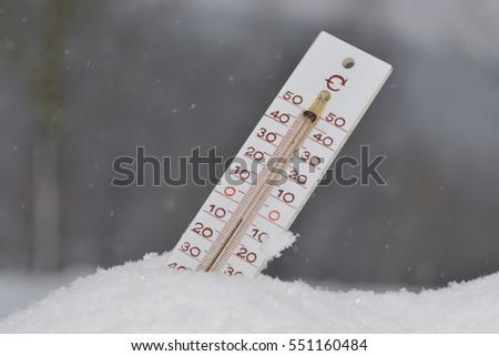 Thermometer in winter in hte snow