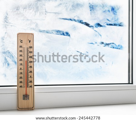 Thermometer on a frozen window and cold weather outside. - stock photo